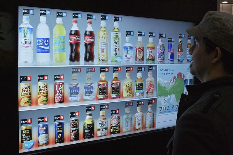 A man standing in front of a vending machine that recommends drinks